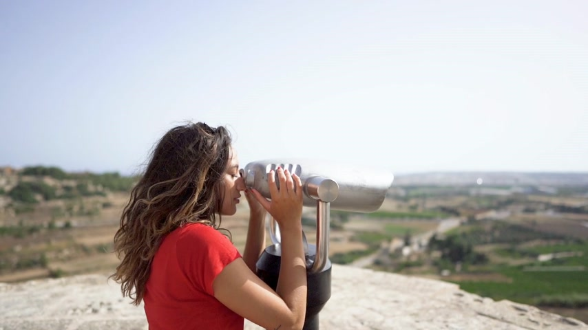 vanishing point : young woman looking through binoculars at malta mdina city Stock Footage