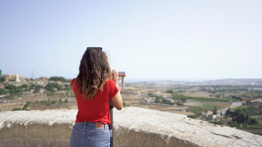 teleskop : young woman looking through binoculars at malta mdina city Stok Video