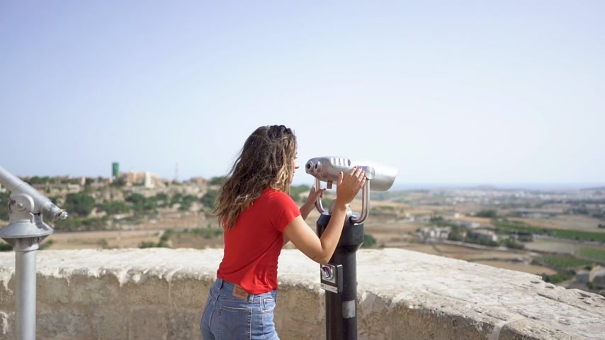 young woman looking through binoculars at malta mdina city Stock mozgókép