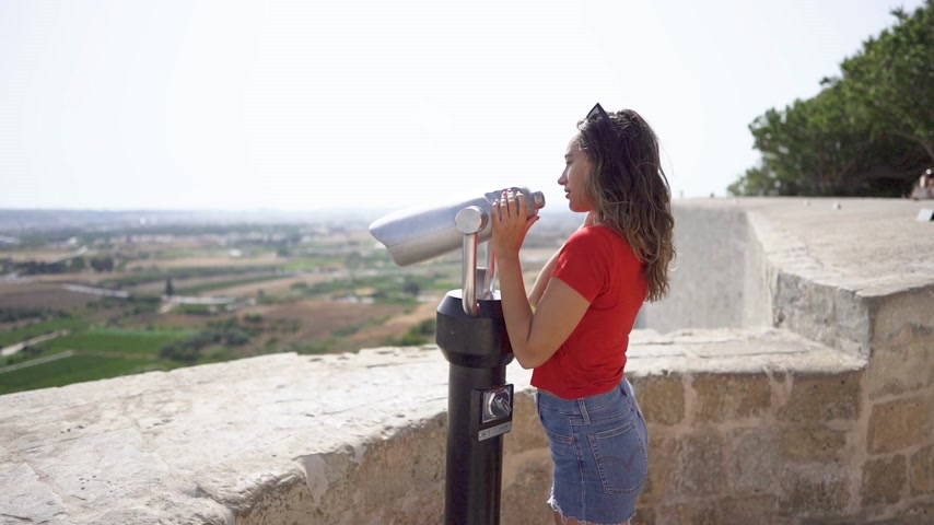 vanish : young woman looking through binoculars at malta mdina city Stock Footage