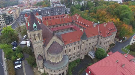 grande angular : Aerial top view beautiful castle in Prague with city view and forest in autumn. Cars passing by on the road. The sky is overcast with leaden clouds. Autumn forest pleases with its colors. Vídeos