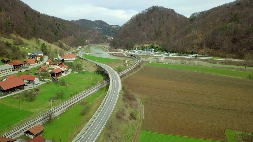 otoyol : Aerial: Flying towards railway and road crossing beside small village. River and water filtration plant in background. Stok Video