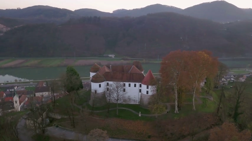 ismert : Aerial: flying around castle of city Sevnica beside river Sava in Slovenia. Beautiful small city with castle is the birth place of first lady Melania Trump.