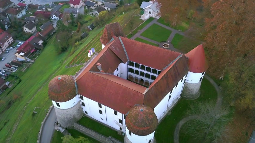 un : Aerial: flying around castle of city Sevnica beside river Sava in Slovenia. Beautiful small city with castle is the birth place of first lady Melania Trump.