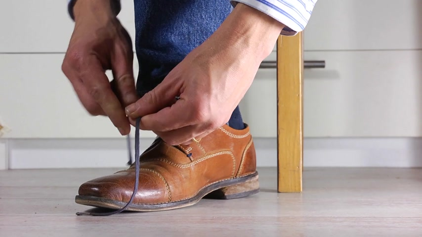 koronka : Close up of a man wearing jeans tying the shoe laces of his brown leather shoes, booth feet