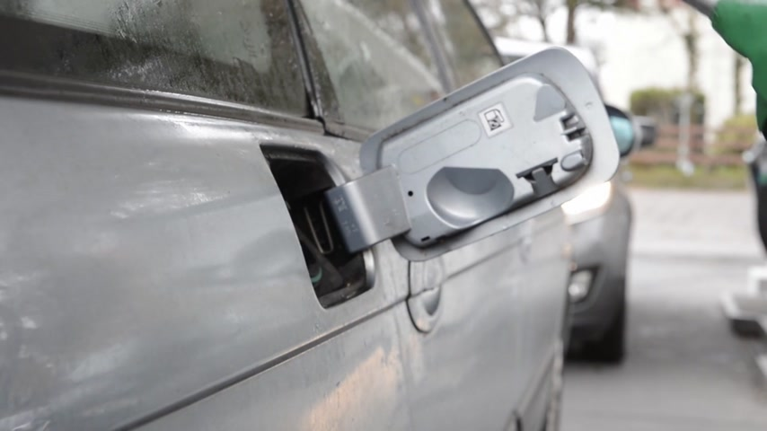 benzin : Man, removing a fuel nozzle from the gas tank of his car, and putting the lid back on