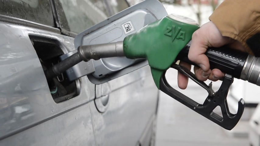 petrol : Man, removing a fuel nozzle from the gas tank of his car, and putting the lid back on