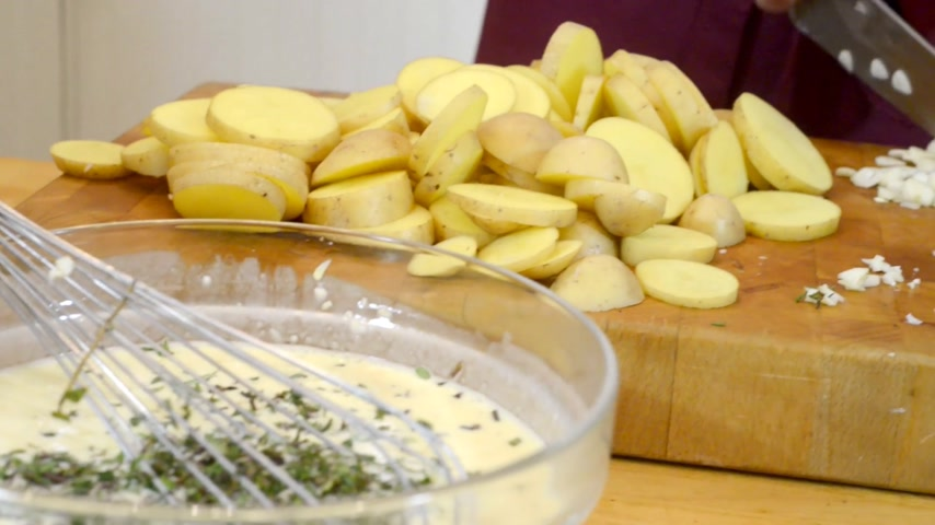 brambory : Pan over a bowl of batter, sliced potatoes, ending at a chef cutting garlic on a cutting board