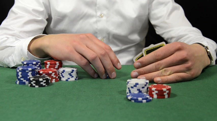 покер : Poker player looking at his cards, fiddling contemplative with his chips, and going all-in Стоковые видеозаписи