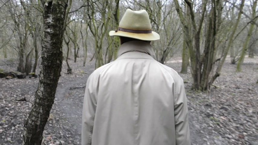 anônimo : Man,  wearing a khaki trench coat and a faded felt hat walking through damp,  grey woods