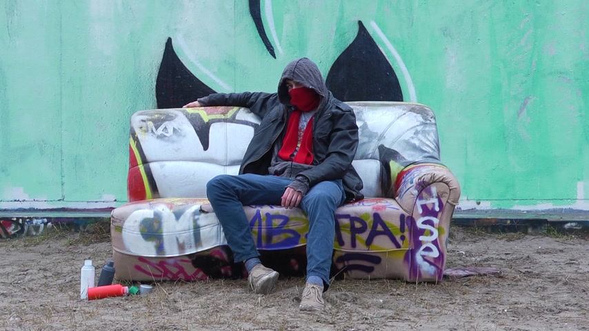 serseri : Graffiti Artist,  sitting on a couch,  relaxing after finishing his artwork,  with a few spray cans on the sand next to him