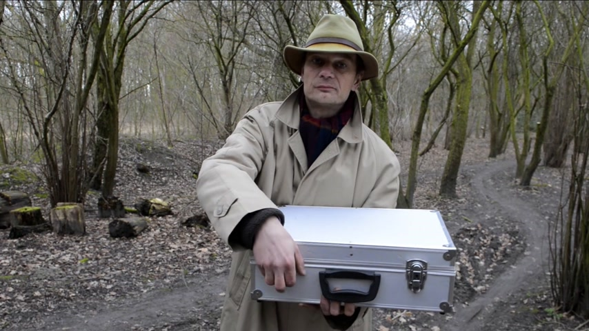 alumínium : Man,  standing in a forest,  opening a large aluminum case filled with money,  displaying it to the camera,  and closing it up again