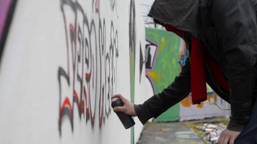 vandalismo : Man,  using spray paint to create graffiti on a concrete wall Stock Footage