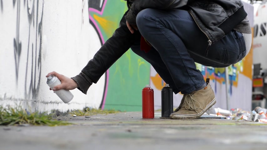 vandalismo : Juvenile delinquent,  using spray paint to create graffiti on a concrete wall Stock Footage