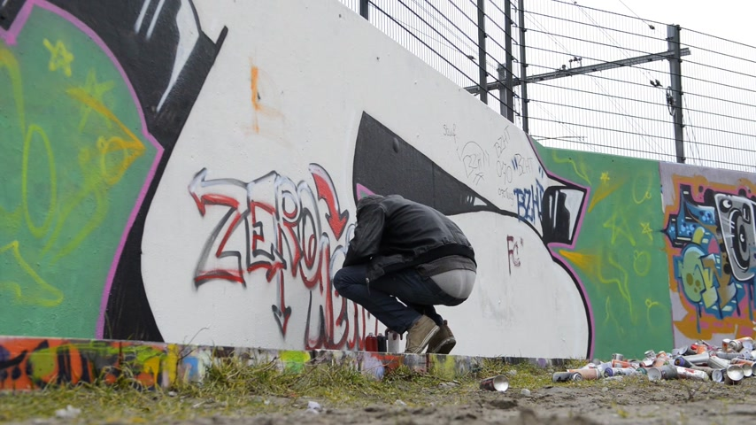 vandalismo : Graffiti artist being disturbed during spray painting,  looking up from his work and running away