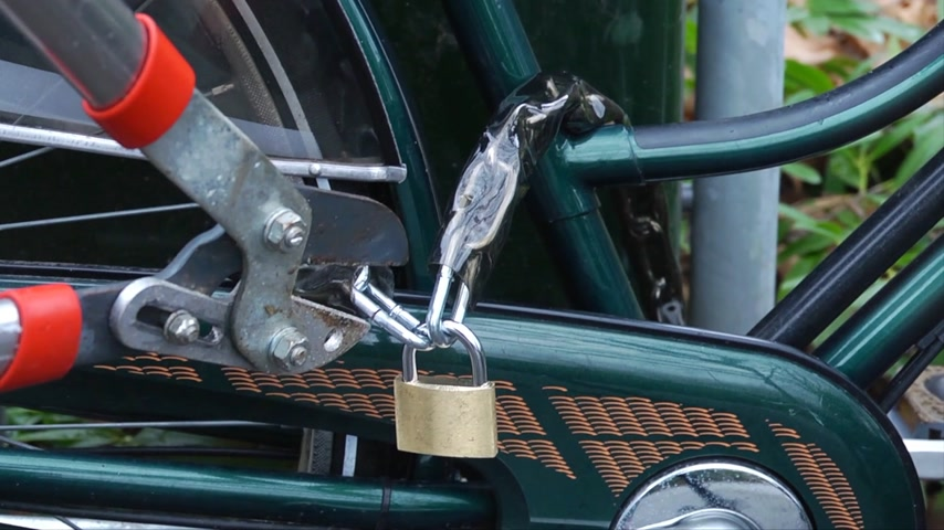 ladrão : Close up of someone stealing a bike by cutting the lock of a bicycle with a bolt cutter.