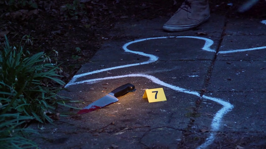 vizsgálat : Forensic scientist taking a blood sample from a kinfe, the murder weapon,lit by the glow of a flash light at a crime scene at night