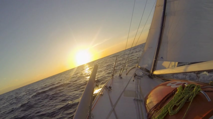 winch : Small racing yacht sails westbound over the Atlantic Ocean towards a beautiful sunset Stock Footage