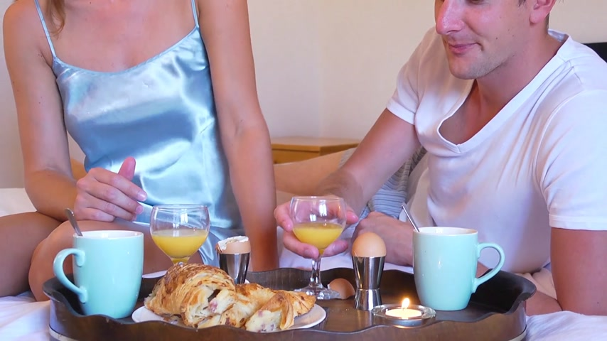 еда и питье : Pan up from a wooden tray with coffee mugs, croissants eggs and orange juice on the white sheets of a bed, to a pretty young couple, enjoying a breakfast in bed together on a sunday morning