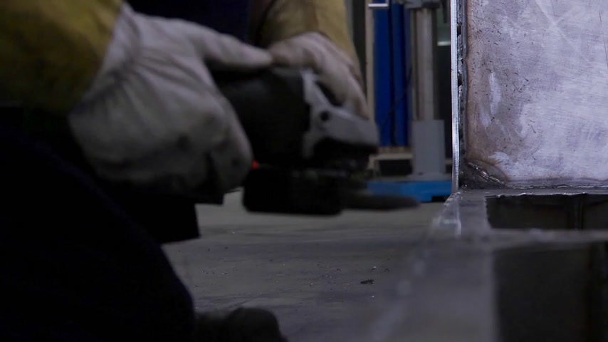 estruturas : Sparks flying off a metal workpiece when a man with a grinding machine touches its surface to deburr weldmarks Stock Footage