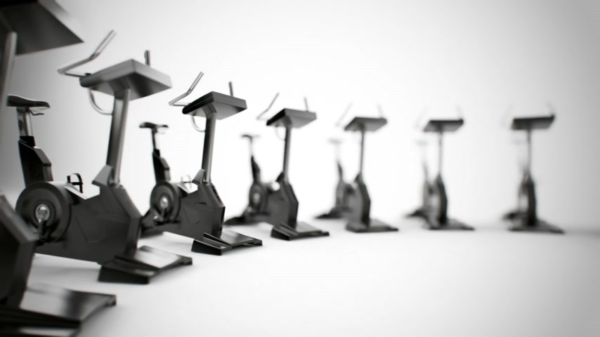 safe workout : Gym equipment stationary bikes. Exercise bicycle, exercycle is a device used as exercise equipment. Stock Footage
