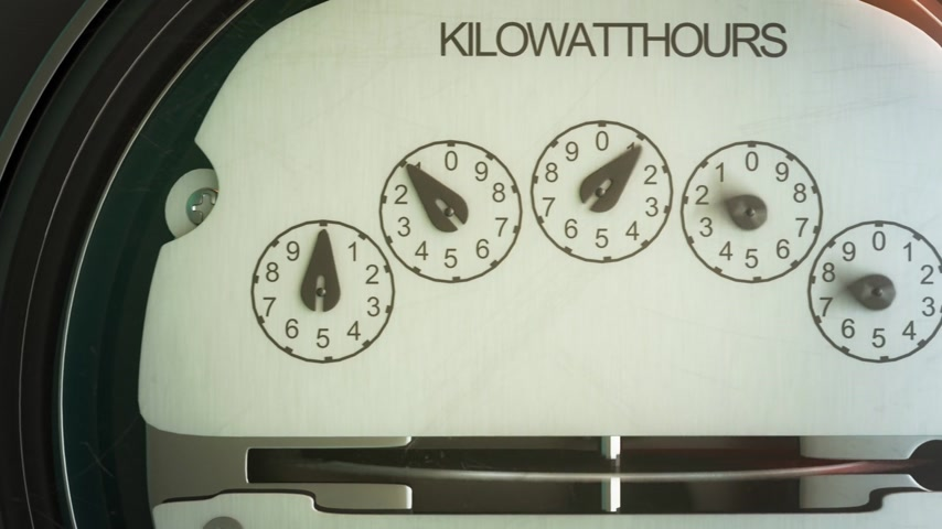 mennyiség : Typical residential analog electric meter with transparent plactic case showing household consumption in kilowatt hours. Electric power usage. Stock mozgókép