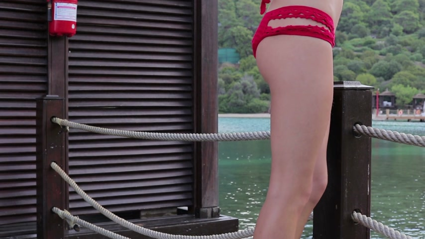 sea piece : Girl in a red swimsuit walking around the island