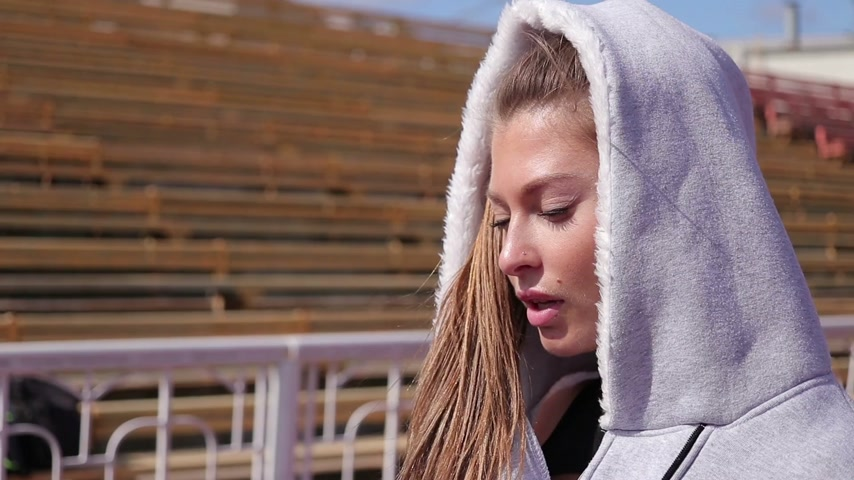 Slim athletic woman putting on earphones while standing on athletic field