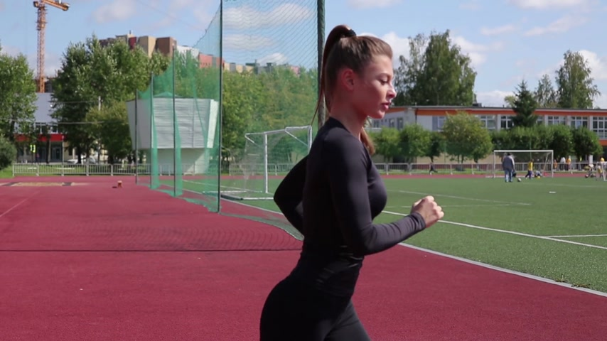 Slim woman running in city stadium Стоковые видеозаписи