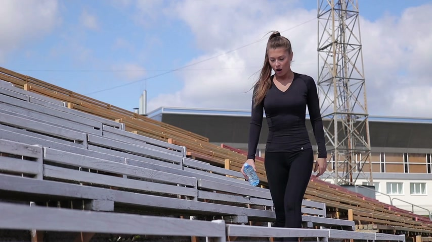 Joyful tired woman in sportswear resting and drinking water after workout in stadium