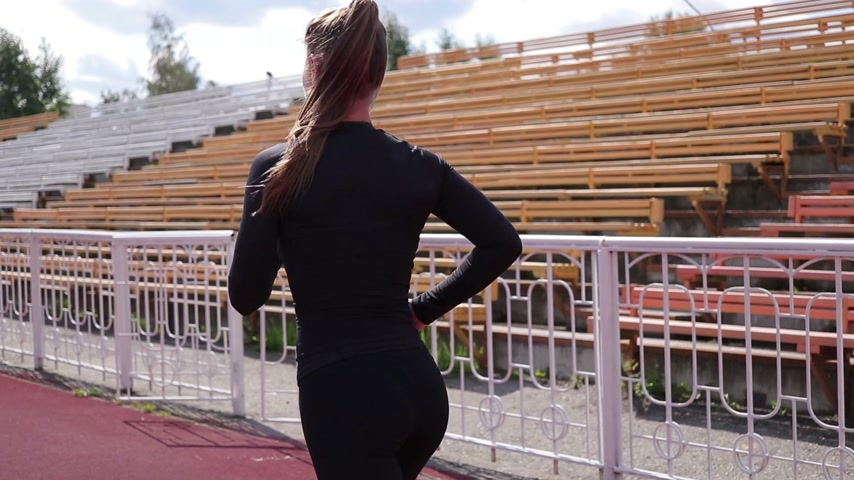 Slim woman running on racetrack in sunshine Стоковые видеозаписи