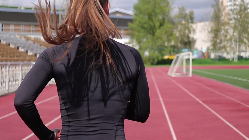 kardio : Slim woman running on racetrack in sunshine Dostupné videozáznamy