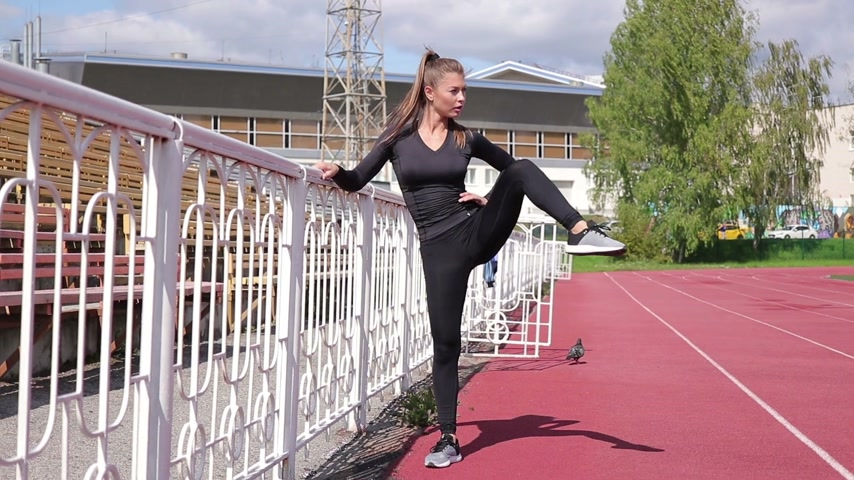 souplesse : Graceful slim woman warming up at city stadium