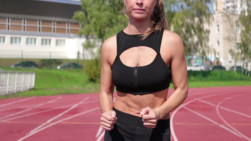 concentrato : Slim sweaty woman running on athletic field Filmati Stock