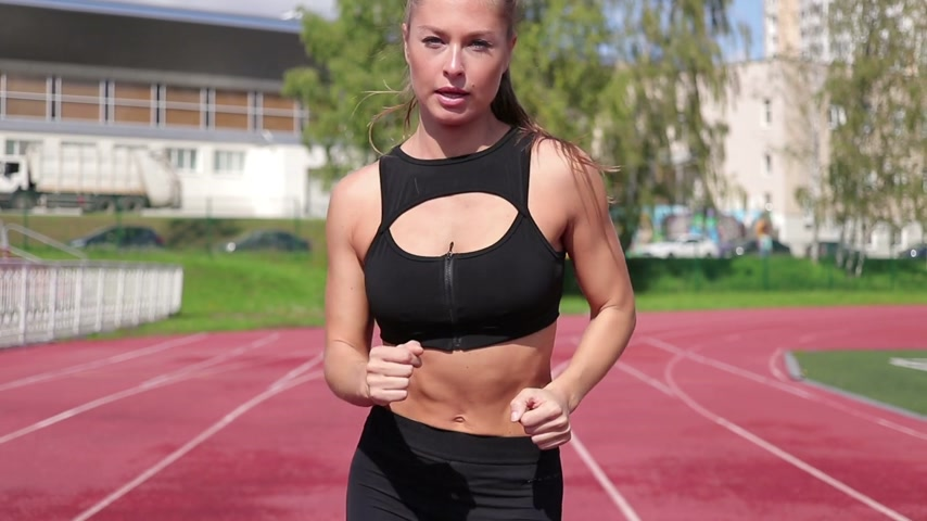 зелень : Slim sweaty woman running on athletic field Стоковые видеозаписи
