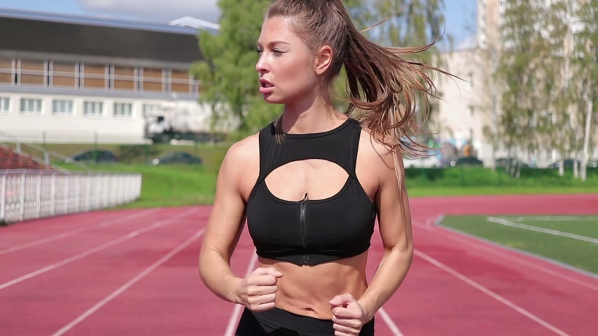 kardiyoloji : Slim sweaty woman running on athletic field Stok Video