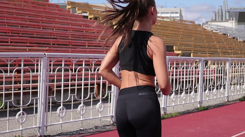 életerő : Slim sweaty woman running on athletic field Stock mozgókép
