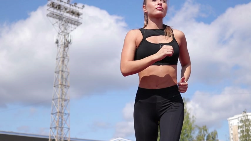 kardio : Slim sweaty woman running on athletic field Dostupné videozáznamy