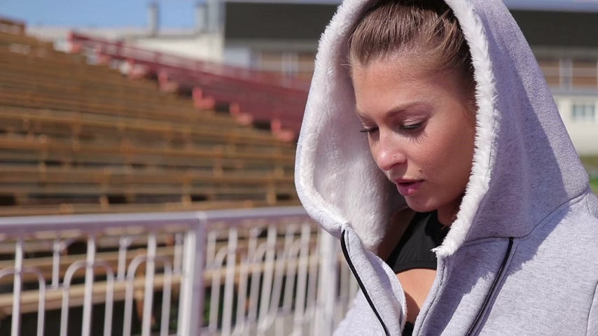 descontraído : Slim athletic woman putting on earphones while standing on athletic field