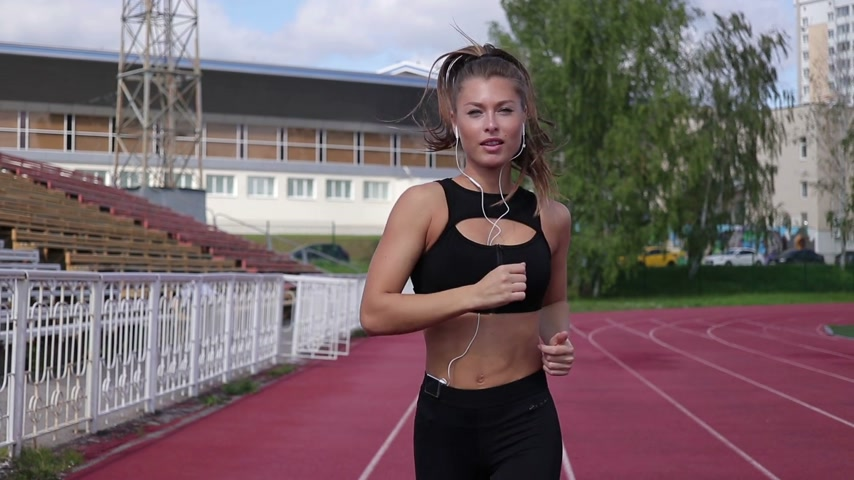 Slim sweaty woman running on athletic field Стоковые видеозаписи