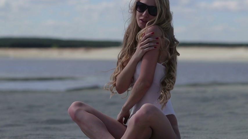 пляжная одежда : Charming woman sitting on beach and making body wave