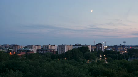por que : Time lapse from the Swedish capital, Stockholm. At nightfall. We see a lot of greenery, the moon, buildings under construction and passing vehicles.
