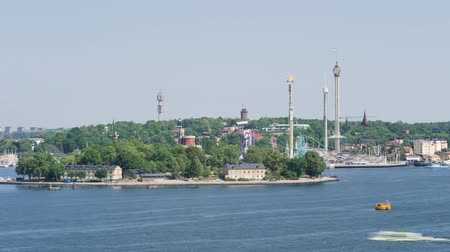 zmarszczki : Time Lapse in the Swedish capital, Stockholm. We see an amusement park (called Gröna Lund) on an island called Djurgården. Ships pass by the island. Wideo