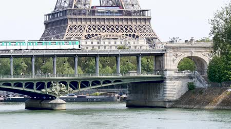 bir hakeim : The bir-hakeim bridge is a famous Parisian bridge which is sometimes used as scenery for movies. Behind it is the first floor of the Eiffel Tower. A subway is passing over the bridge. Filmed with a long focal length.