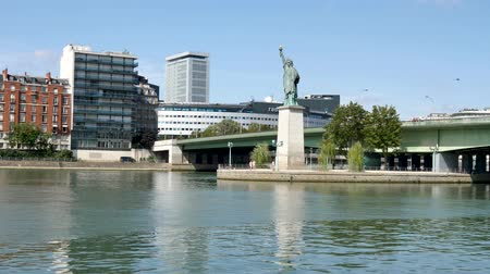 perçin : Statue of Liberty in Paris. The statue is smaller than the one in New York. It is located on a small island in the Seine. Front view. Grenelle bridge (parisian bridge) behind the statue.
