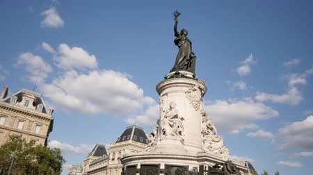 Paris during the summer. Time lapse on the Place de la Republique (famous city square). In the center a large statue, which represents the republic. People pass around. Clouds moving behind the statue. Стоковые видеозаписи