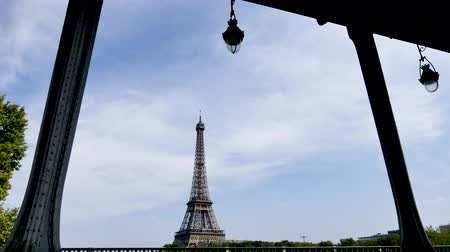 bir hakeim bridge : Paris in summer. From the bir-hakeim bridge you can see the Eiffel Tower behind the Seine. Lamps are hung on the arches of the famous bridge, which is often used as film scenery. Cars are passing over the bridge.