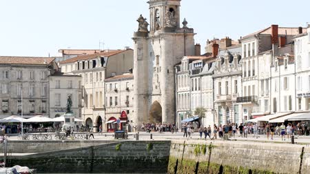 Западная Европа : City center of La Rochelle, a seaport on the Atlantic coast in western France. Its a street near the old port. Filmed during the summer. The clock tower is a gate to the old city.