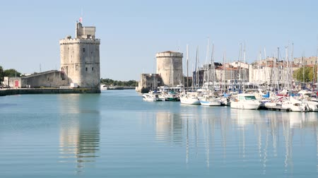 типичный : The famous towers of the old port of La Rochelle, a town in western France, located in the Charente-Maritime department. Boats are moored.