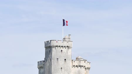 Западная Европа : French flag over a tower of the old port of La Rochelle, a French town in western France. Filmed during the summer. The tower is called in French Saint-Nicolas.